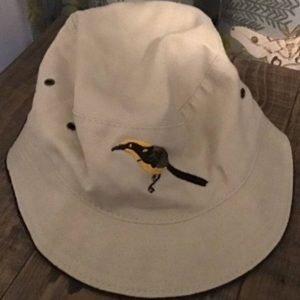 beige bucket hat with emrboidered helmeted honeyeater image